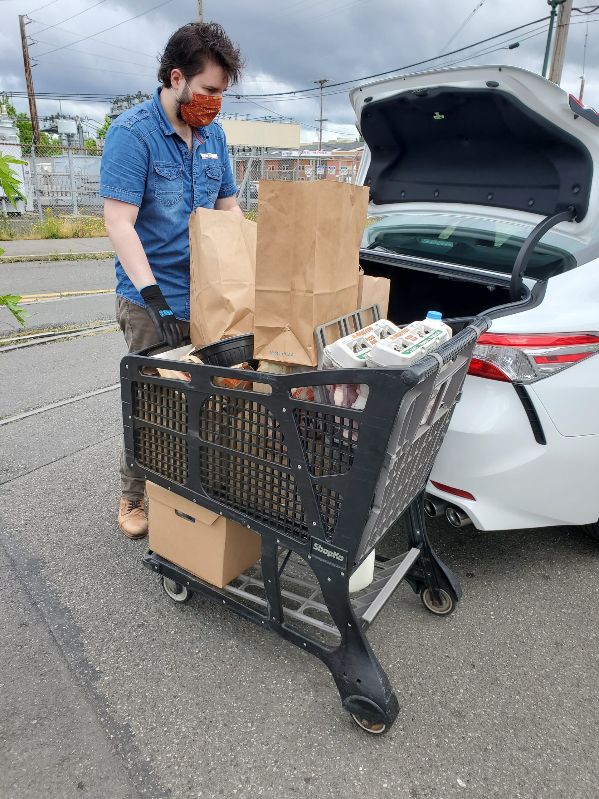 Phot of man loading groceries into a car.